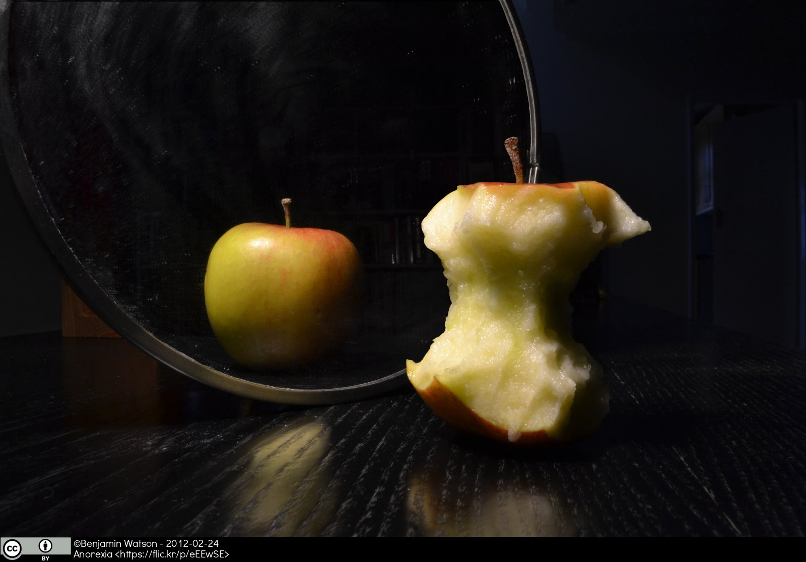 A whole apple and a partially eaten apple